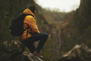 Ein Mann schaut in die Berge in seiner Hardshelljacke