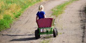 Ein Kind, das einen Bollerwagen zieht.