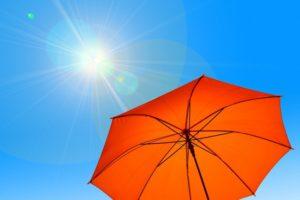 orangener Sonnenschirm und eine Sonne