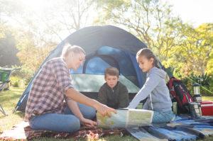 Mutter sitzt mit ihren zwei Kindern vor einem Zelt