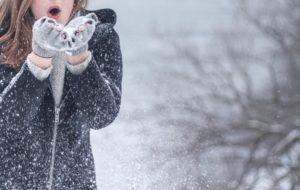 Eine Frau, die Schnee aus ihren beheizten Handschuhen bläst.
