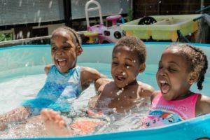 Drei Kinder in einem Planschbecken.