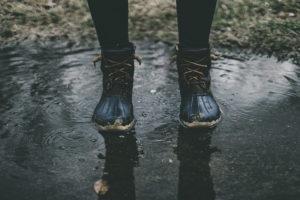 Person steht bei Regen in einer Pfütze