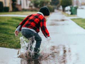 Ein Kind spielt in einer Pfütze