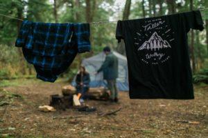 Von Camping-Waschmaschine gewaschene Wäsche auf Leine vor Zelt